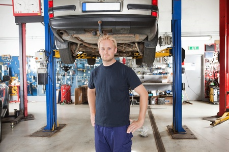 Portrait of smiling young mechanic standing inside his auto repair shop photo