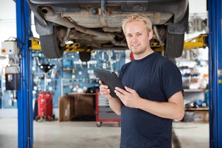 hijsen: Portret van jonge mechanische bedrijf digitale tablet in zijn auto reparatiewerkplaats Stockfoto