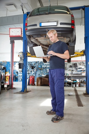 service lift: Full length portrait of young mechanic using laptop in his auto repair shop