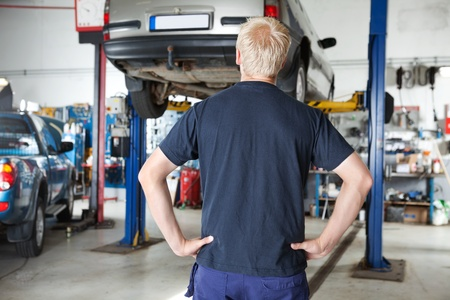 car workshop: Rear view of car repairer looking at car in auto repair shop with hands on waist