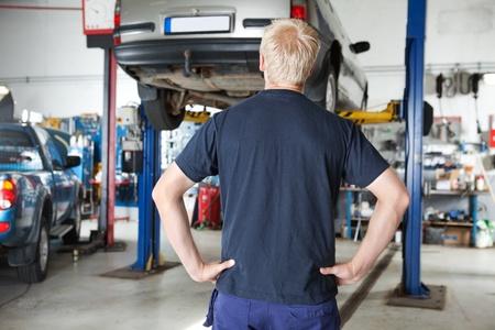 garage automobile: Vue arrière de la voiture réparateur regardant voiture en atelier de réparation automobile avec les mains sur la taille Banque d'images