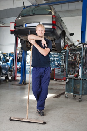 shop skill: Full length portrait of young man leaning on broom in garage