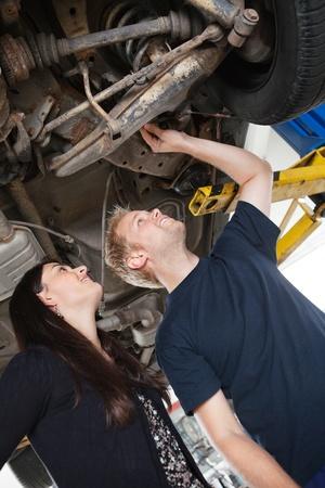 garage automobile: Mécanicien montrant les problèmes des clients féminins avec la voiture Banque d'images