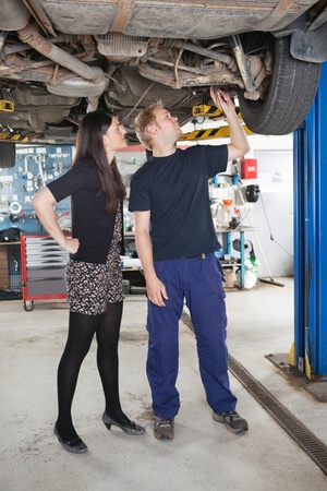 Young male mechanic and woman looking at underboy of car in auto repair shop photo
