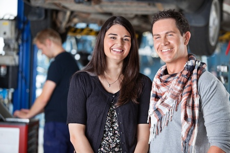Portrait of smiling young couple in auto repair shop with mechanic in the background photo