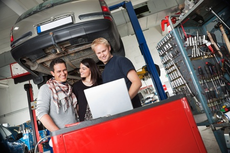 Young couple in auto repair shop standing with mechanic looking at laptop photo
