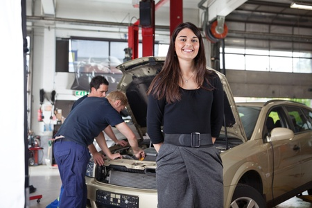 repair shop: Portrait of attractive female in garage while people working in background