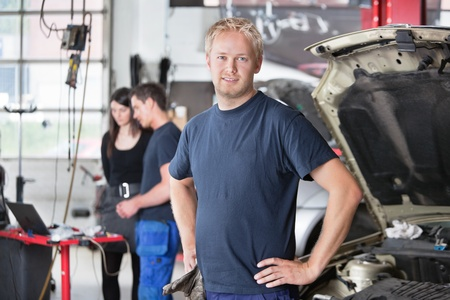 Portrait of a  young mechanic in auto repair shop with customer in background photo