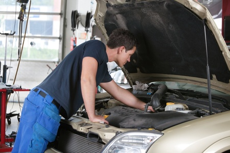 Auto mechanic working on a car in garage photo