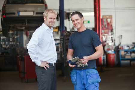 Portrait of a male customer standing with mechanic outside the garage photo
