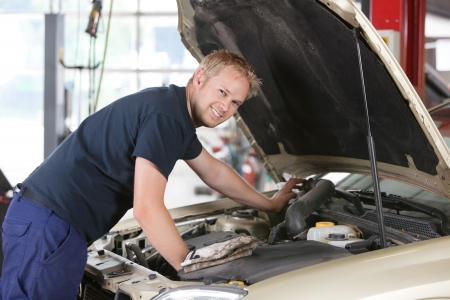 motor show: Portrait of a smiling mechanic working on a car in garage
