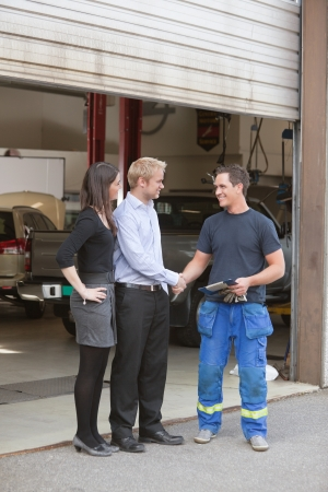 Full length of mechanic shaking hands with client outside garage photo