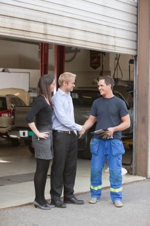 garage automobile: Pleine longueur de mécanicien se serrant la main avec le client en dehors de garage