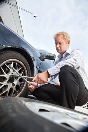 Business man changing a tire on the street photo