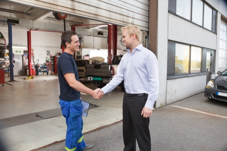 two car garage: Candid portrait of a mechanic shaking hands with client Stock Photo