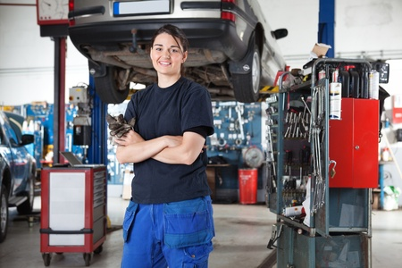 auto lift: Portrait of smiling young female mechanic with arms crossed in auto repair shop