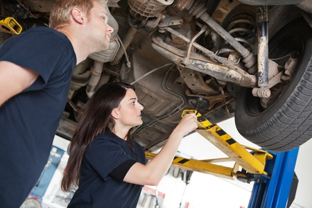 suspension: Two mechanics looking at a car discussing a problem