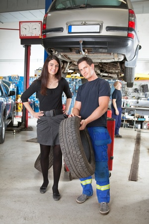 Full length portrait of female customer and mechanic holding tire in hand photo
