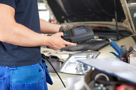 Mid section of mechanic holding a diagnostic tool photo