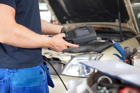 herramientas de mec�nica: Secci�n media de mec�nico sosteniendo una herramienta de diagn�stico