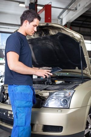 Mechanic working on a digital tablet while standing besides car photo