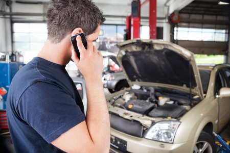 Mechanic talking on cell phone in garage photo
