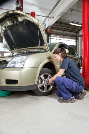 Female mechanic changing wheel of car with pneumatic torque wrench photo
