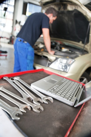 Closeup of a laptop and wrench and man mechanic working in background photo