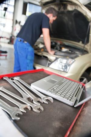 herramientas de mec�nica: Primer plano de un ordenador port�til y una llave mec�nica y un hombre que trabaja en segundo plano Foto de archivo