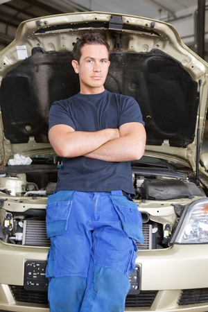 Portrait of a man mechanic leaning against a car looking at the camera photo