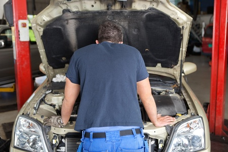 Rear view of mechanic working on a car in garage photo