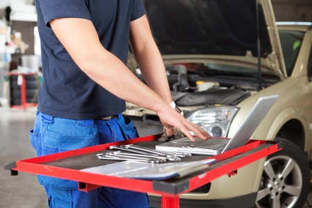 livelihood: Mid section of mechanic working on laptop in a garage Stock Photo