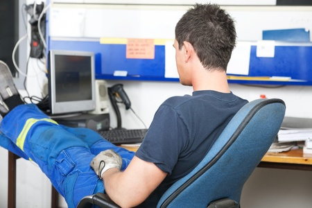 Mechanic sitting at desk in auto repair shop photo