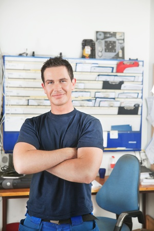 Portrait of a handsome smiling mechanic with arms crossed photo