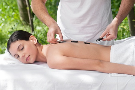 Young woman getting a hot stone massage at spa salon photo
