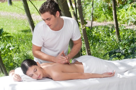 masseuse: Woman receiving massage outdoors from professional masseuse Stock Photo