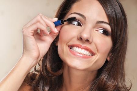 Hermosa mujer sonriente de aplicar el rimel en sus pestañas