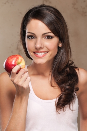 girl apple: Close-up portrait of young beautiful woman holding an apple