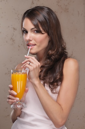 Smiling portrait of an attractive woman drinking orange juice photo