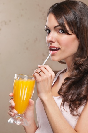 Close-up portrait of beautiful woman drinking orange juice with straw photo