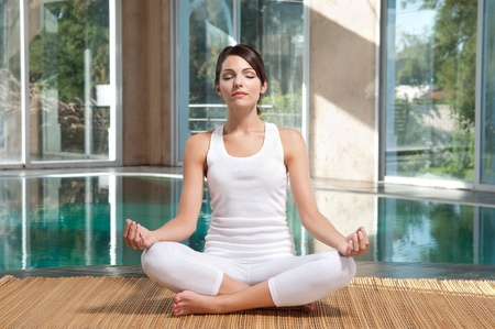 Pretty young woman with eyes closed doing yoga exercise on mat photo