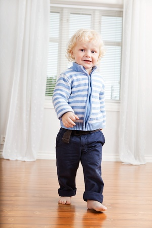 Full length of cute little boy walking on floor at home Stock Photo - 10451841