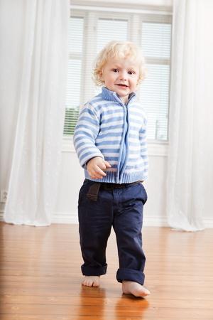 toddler walking: Full length of cute little boy walking on floor at home Stock Photo