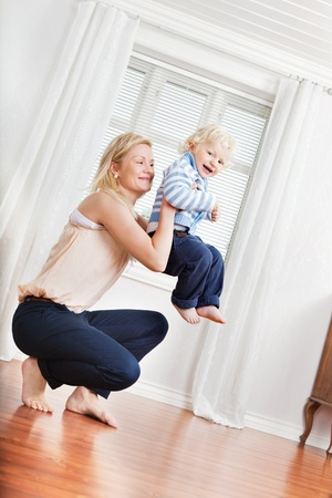 Full length of young mother playing with cute boy photo