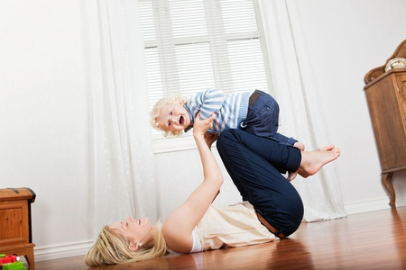 Cheerful mother playing with her cute loving baby boy at home Stock Photo - 10700535