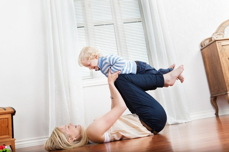 two floors: Happy mother playing with her cute loving baby at home Stock Photo