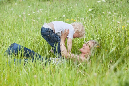 Young pretty woman holding her child while lying on grass photo