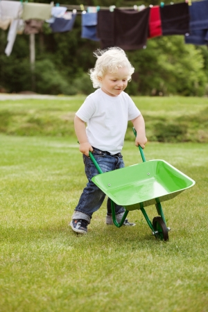 barrow: Cute young baby boy pushing a wheelbarrow in garden with clothes hanging in the background