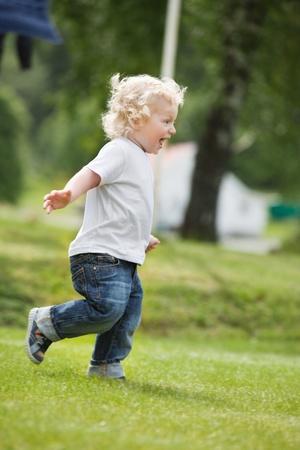 niño corriendo: Longitud total de niño feliz corriendo en el jardín con la boca abierta