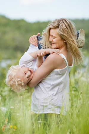 An attractive young woman playing with sweet little boy in green meadow photo